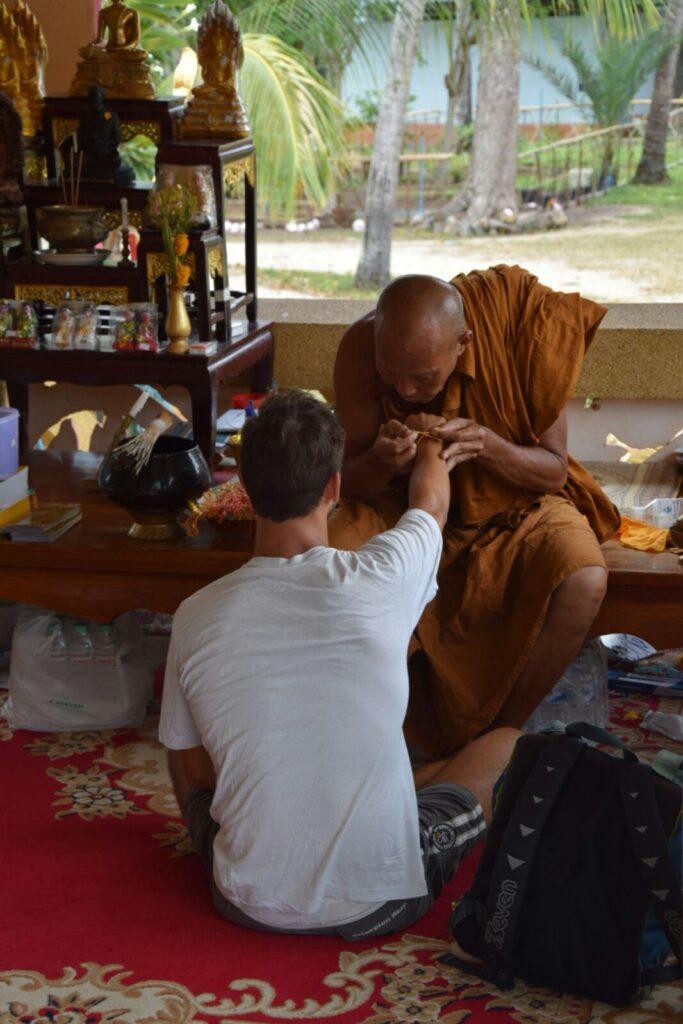 Il monaco buddhista mentre mi stringe un braccialetto